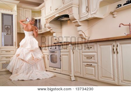 Beautiful Bride Stands In The Kitchen