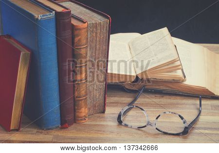 Books and glasses on wooden table background, retro toned