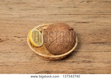 Coconut and a slice of lemon in a wicker basket on an old wooden table
