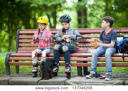Three children resting after skating in park