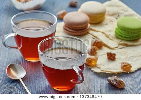 Two glass cup of black tea and three colorful macaroons on wrapping-papper