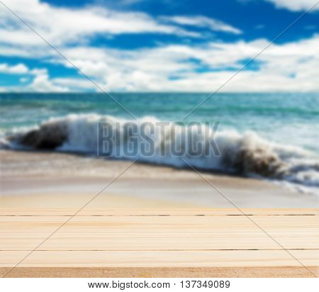 Wood table top on blurred sea and beach storm with sky and cloud storm