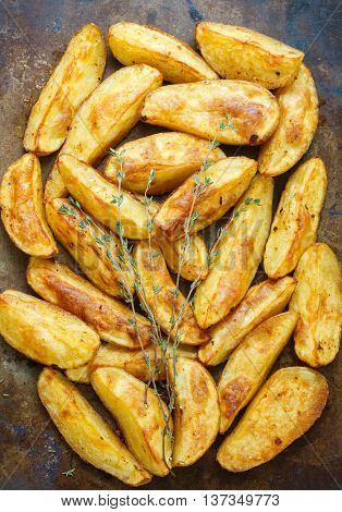 Baked potato wedges with spices and thyme on a metal baking sheet. Top view