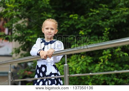 Portrait of a little girl. Child in a beautiful dress looking to side hands on railing. Green tree in background.