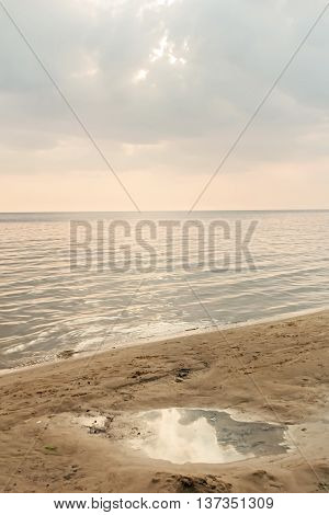 Puddle in sand on seashore at summer sunset