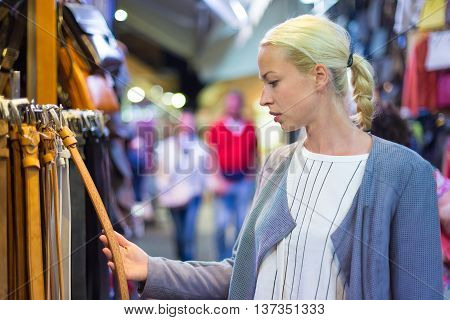 Beautiful casually dressed caucasian blond woman shopping for new leather belt on crafts market in Chania, Crete, Greece.