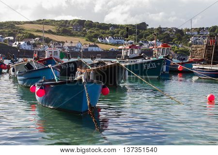 COVERACK, CORNWAL, UK - JULY 1, 2016. Rows of colourful, Cornish fishing boats floating in the calm harbour of Coverack in Cornwall.