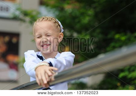 Portrait of a little girl. Child in a beautiful dress looking to side hands on railing. Green tree in background. little girl laughs