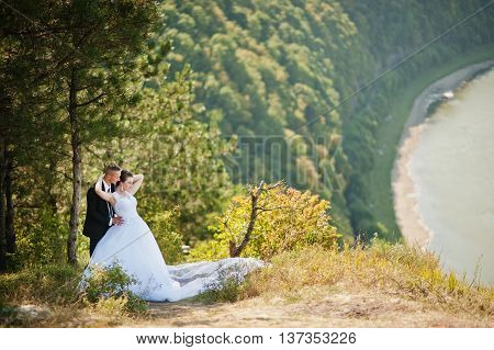 Wedding Couple On Panorama Of City And River. Bride With Long Veil