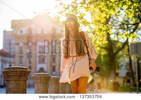 Young female traveler dressed casual with hat and sunglasses walking on Congress square in Ljubljana city at the sunny weather. Traveling in Slovenia