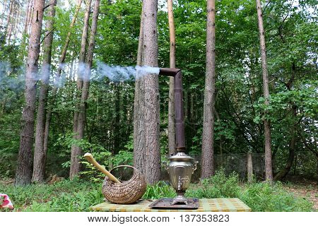 in the forest in a clearing on the table is a samovar and it boils water