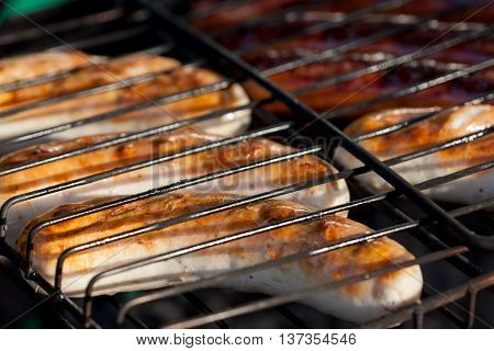 Tasty sausages are fried on a grill