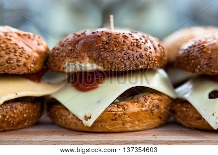 Some of appetizing cheeseburgers on a wooden board