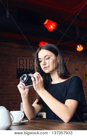 Young Girl Photographer With Old Analog Camera In Cafe