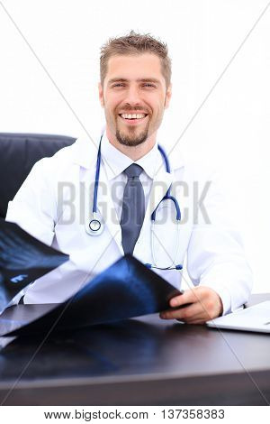 Middle-aged doctor looking at an x-ray isolated on white background