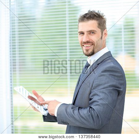 Business man using tablet in an office against the window