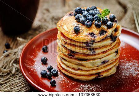 Blueberry Ricotta Pancakes on a dark wood background.