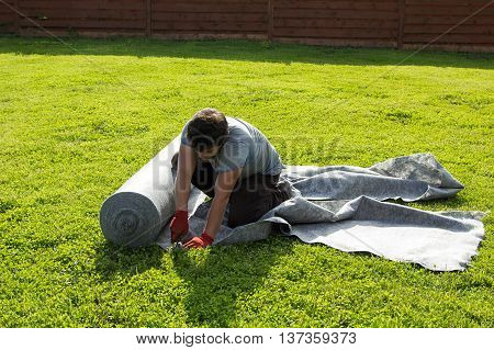 Man Cut Geotextile On The Lawn