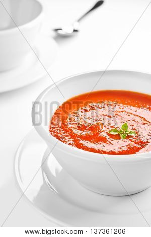 Picture of a white bowl with tomato cream soup with basil leaves on top shallow depth of field.