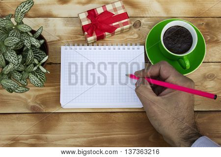Writes a note a gift with a Cup of coffee on a wooden table