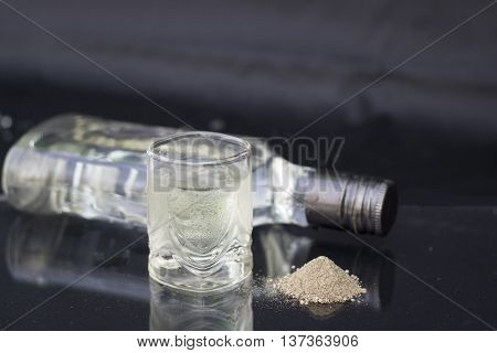 A glass of vodka on ice on black background black ground pepper
