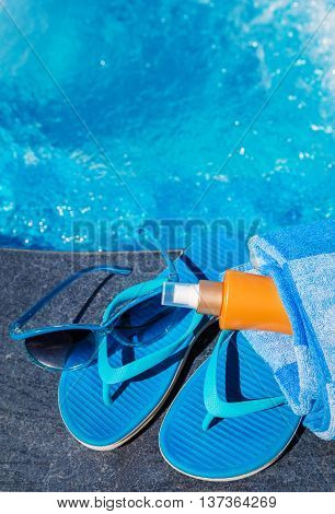 Blue Slippers, Sunsscreen Cream And Sun Glasses Near Swimming Po