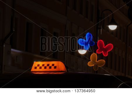 Close-up yellow illuminated taxi sign at night near the bright street lamp in the form colorful butterflies, artistic light effect blur.