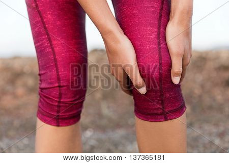 Runner woman gripping painful hurt knee pain. Athlete woman running outside with body injury. Closeu
