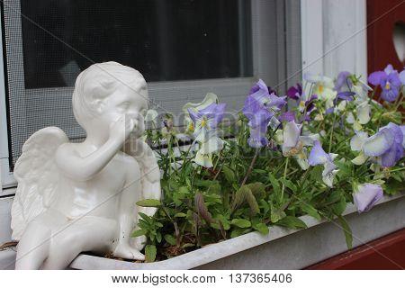 Ceramic angel whispering in flower box by window