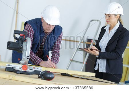 carpenter writing on blueprint woman watching from background