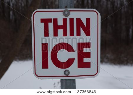 Sign warning of Thin Ice in a pond