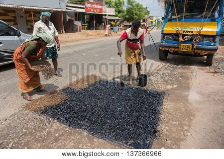 Madurai India - October 18 2013: A crew of two men and one woman repair the road in Madurai. Dirt and stones to fill the lowness in the road and then liquid tar to cover it.