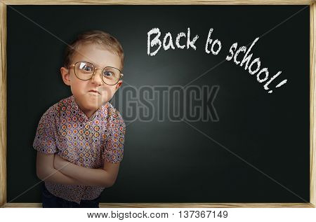 Emotional irritated bespectacled pupil boy near chalkboard