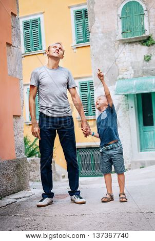 Father with son walk together on the old sity street