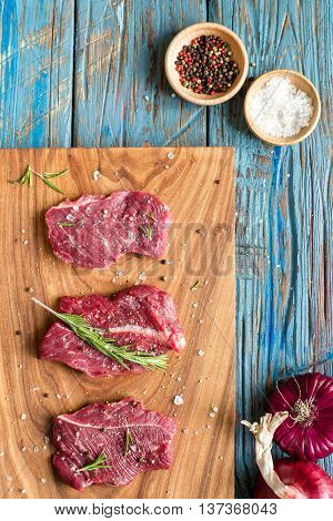 fresh meat on chopping board with rosemary, spices, red onion. Raw meat. three peece of beef ready for cooking on wooden blue table . close up. top view