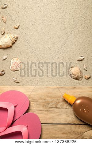Summer concept with pink flip flops suntan oil and shells on sandy beach. Top view