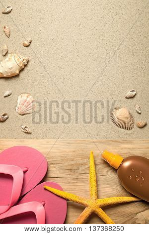 Summer concept with pink flip flops yellow starfish suntan oil and shells on sandy beach background. Top view