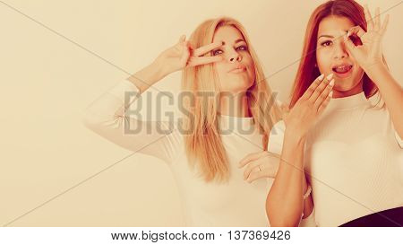 Friends people fashion concept. Two crazy girls playing around together. Young ladies have white blouse. Women posing in funky way.