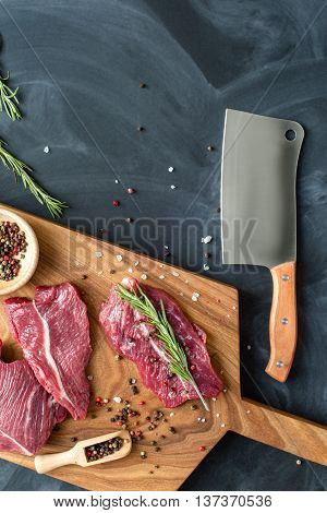 fresh meat on chopping board with rosemary, salt, pepper and knife. Raw meat. three peece of beef ready for cooking on wooden board on black background . close up. top view. place for text