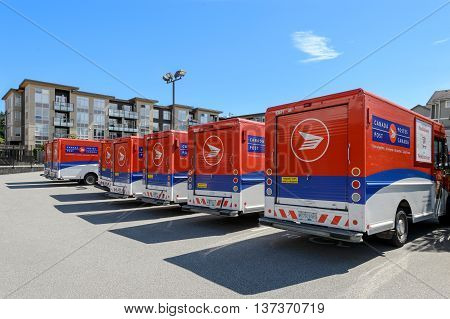 VANCOUVER CANADA - June 12 2016: A line of Canada Post trucks on a parking lot of a central office.