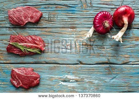 fresh meat with rad onion on blue wooden background. Raw meat. three peece of beef ready for cooking on wooden blue table . close up. top view. colorefull. place for text