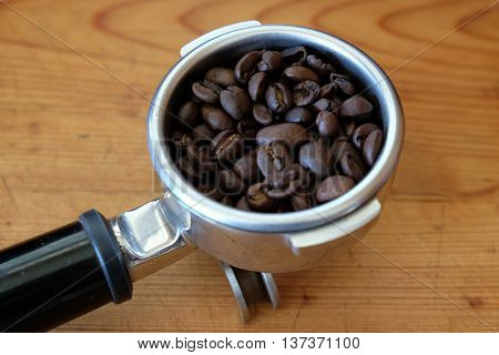 Portafilter filled with whole coffee beans, against a wooden background.