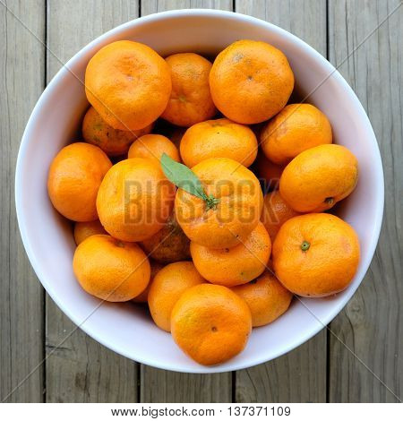 Imperfect blemished organic satsuma mandarins. Citrus fruit is in a white bowl, photographed from above with a wooden background.