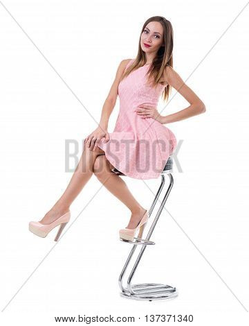 young gorgeous caucasian woman in pink dress on the chair, isolated on white, studio shot