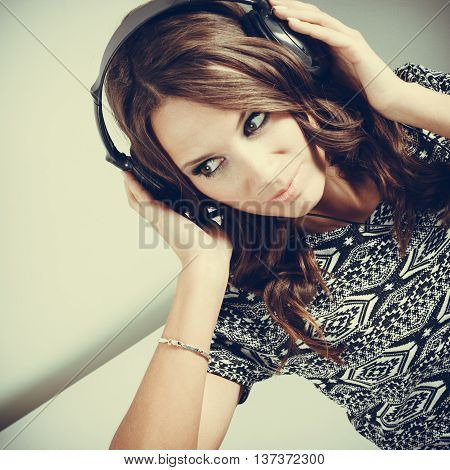 People leisure relax concept. Young woman in big headphones listening music mp3 relaxing toned image