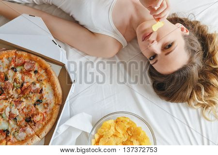 Girl eating chips on the bed, standing next to the pizza. Girl looking at camera lying on white bed