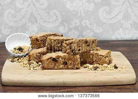 Healthy granola brownies stacked on a cutting board.