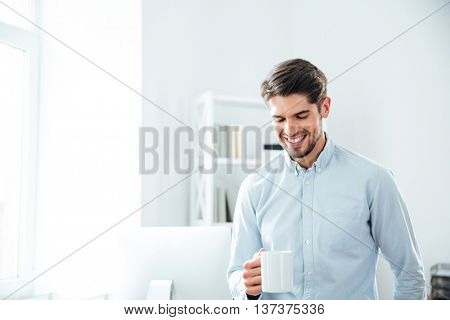 Cheerful young businessman smiling and drinking coffee in office