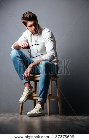 Serious handsome young man in white shirt and jeans sitting and holding sunglasses over grey background