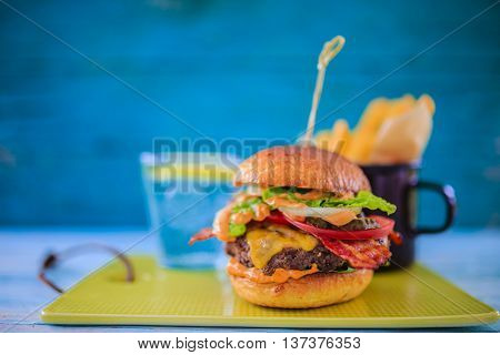 Tasty street food grilled beef burger in crispy shortbread with lettuce and mayonnaise served on small cutting board a rustic wooden table